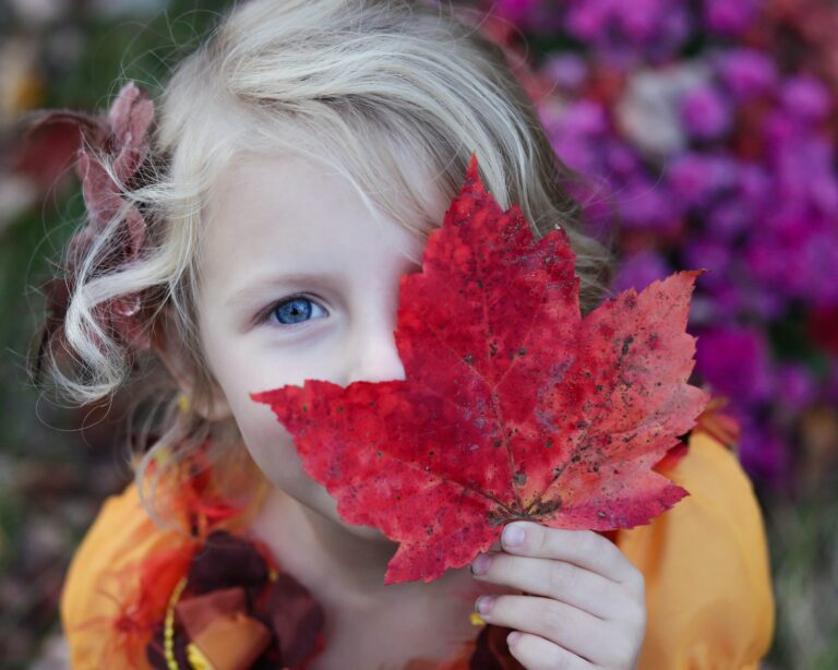 Child holding a leaf over her face