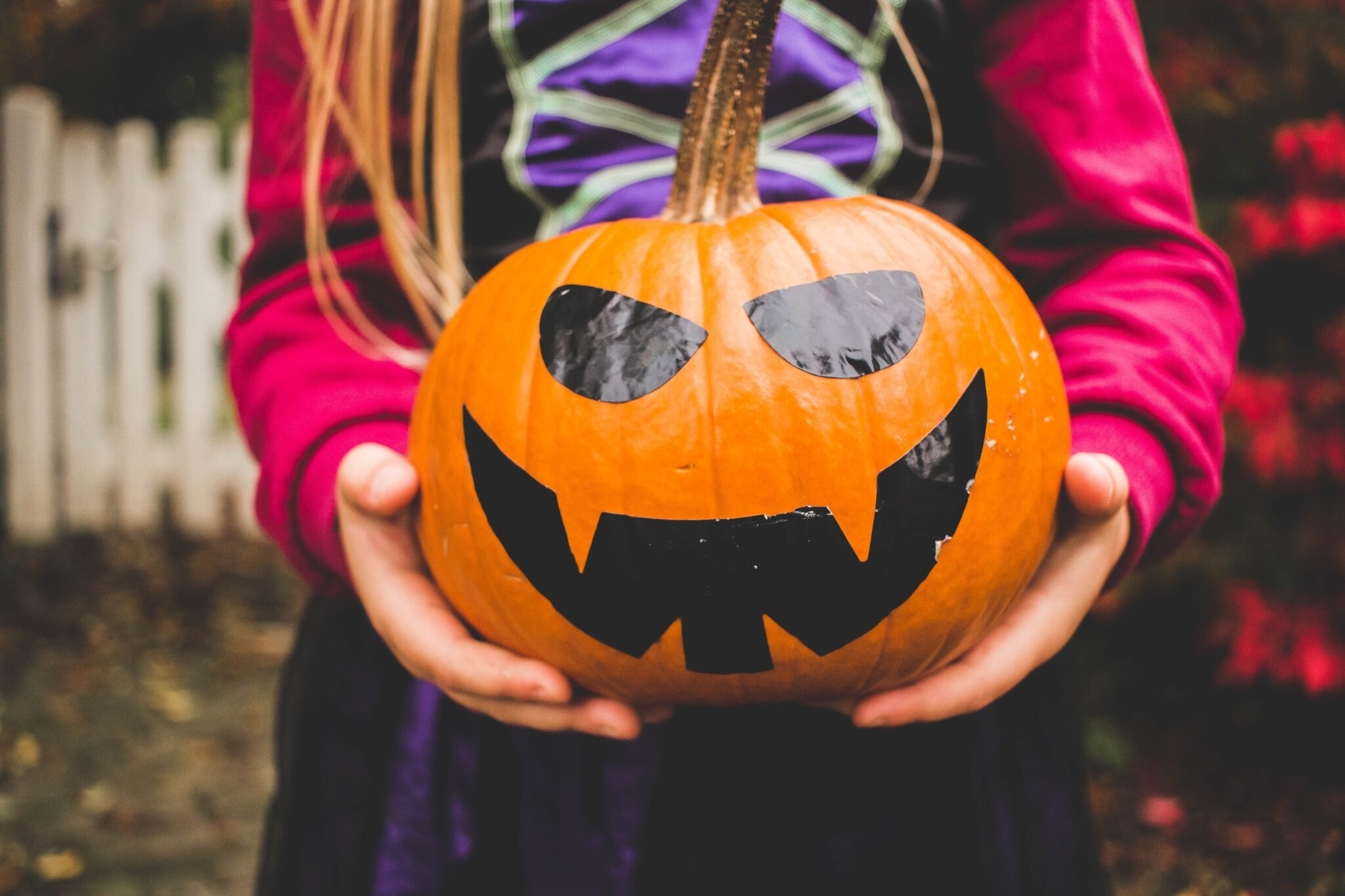 child holding pumpkin with halloween face