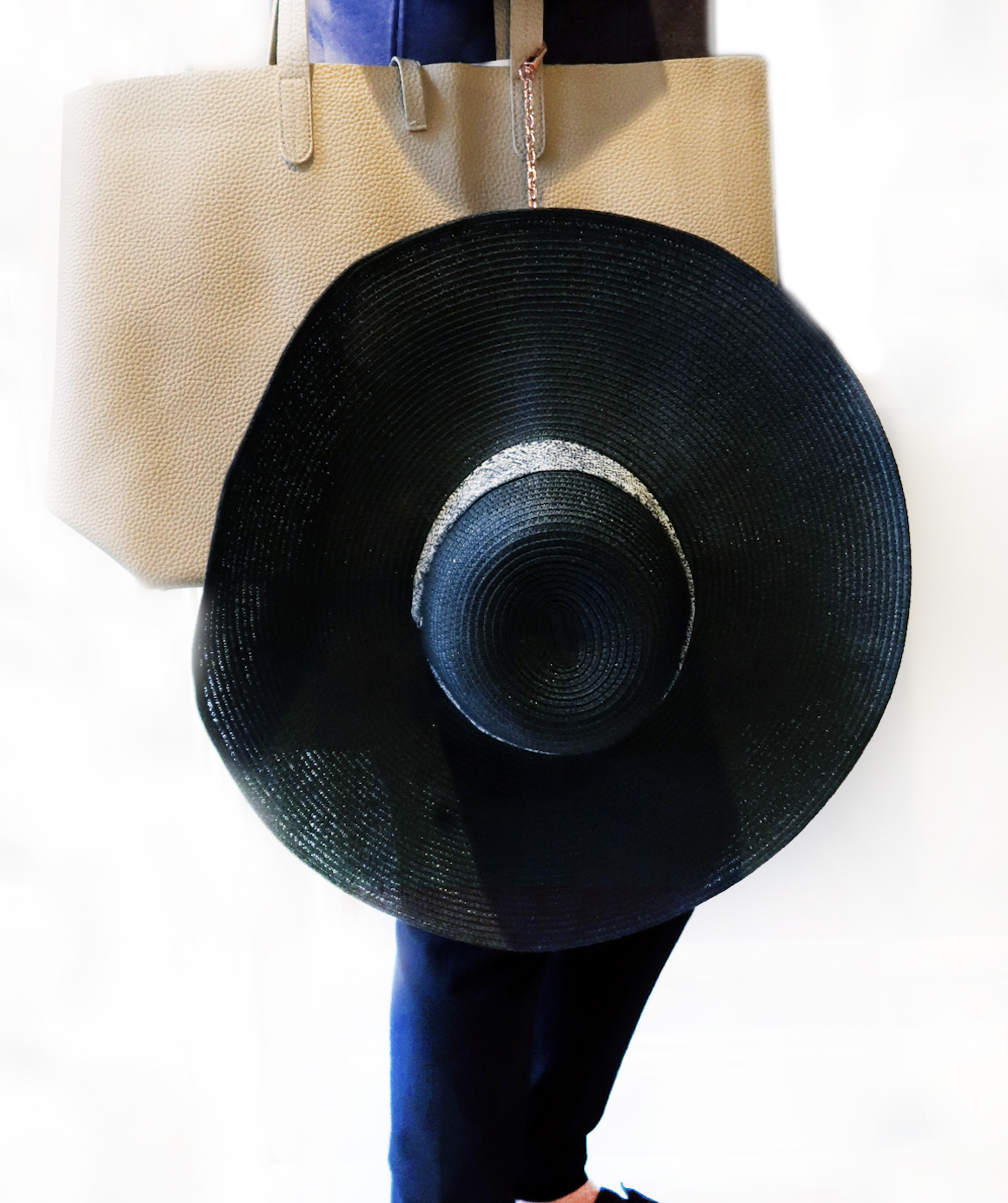 Floppy hat hanging from purse connect by pochette chain strap