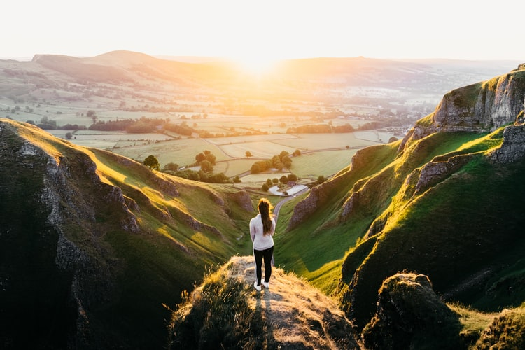 woman standing on a cliff watching the sunset
