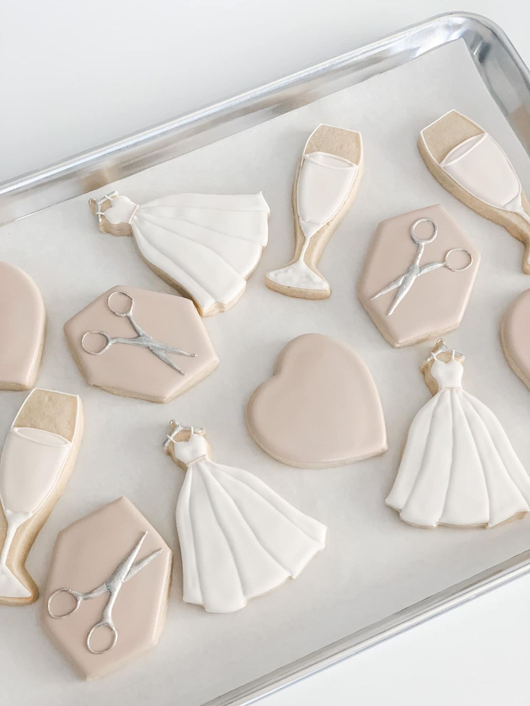 cookies with wedding dresses, scissors and champagne on them
